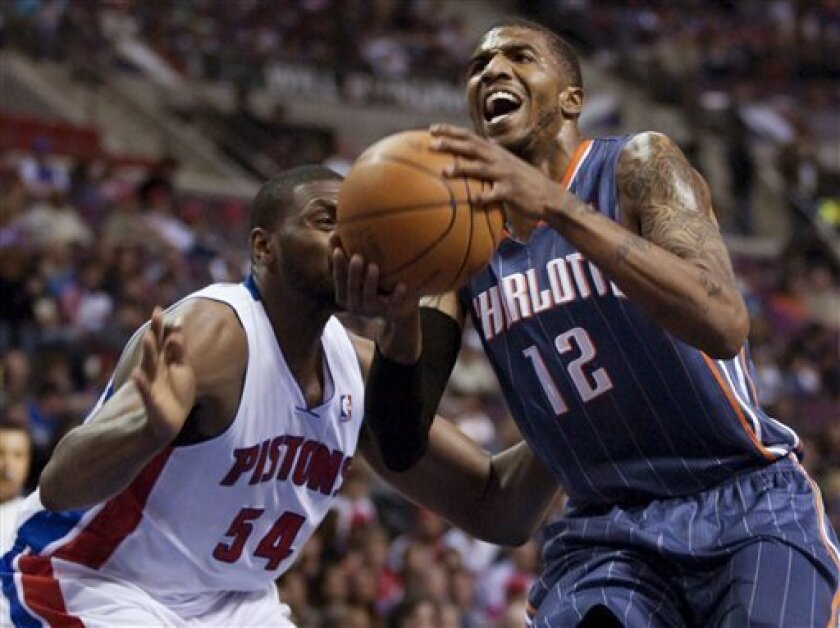 Charlotte Bobcats' Tyrus Thomas (12) goes to the basket past Detroit Pistons' Jason Maxiell (54) in the second quarter of an NBA basketball game Saturday, March 31, 2012, in Auburn Hills, Mich. (AP Photo/Duane Burleson)