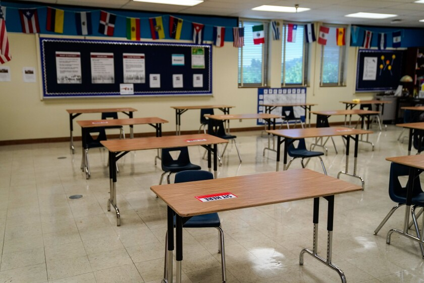 "Tables in an empty classroom have ""Sit Here"" labels to help students with social distancing."