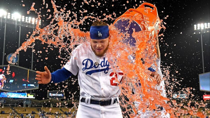 Joc Pederson unloads an ice cooler on Dodgers teammate Alex Verdugo after his sacrifice fly drove in the winning run against the New York Mets on May 29. The Dodgers are winning games and spurring prognostications about their title chances.