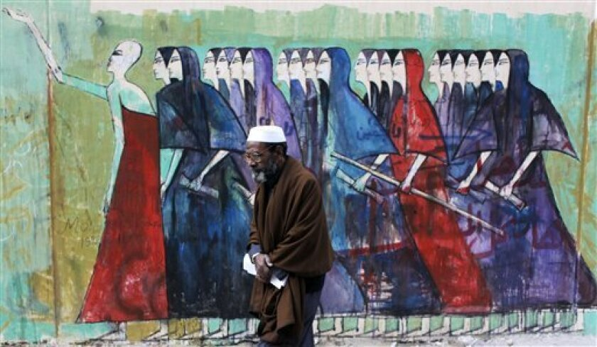 """An Egyptian man passes by a mural and Arabic that reads, """"free men will continue the journey, coming back,"""" in Cairo, Egypt, Thursday, Feb. 9, 2012. Egypt is refusing to back down in a dispute with the U.S. over Cairo's crackdown on nonprofit groups despite Washington's threats to cut aid, while the military deployed troops to the nation's streets after a surge in violence and protests against its rule. (AP Photo/Nasser Nasser)"""