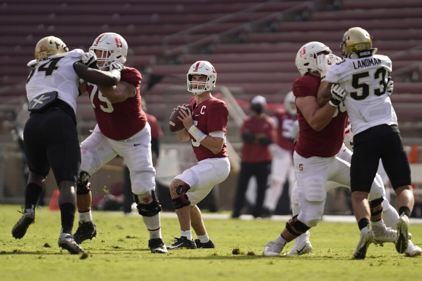 Stanford quarterback Davis Mills, center, looks to pass against Colorado during the first half of an NCAA college football game in Stanford, Calif., Saturday, Nov. 14, 2020. (AP Photo/Jeff Chiu)