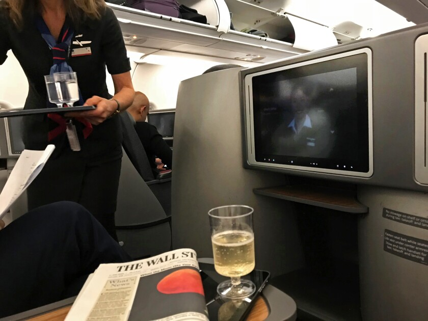 A flight attendant serves a business-class passenger.