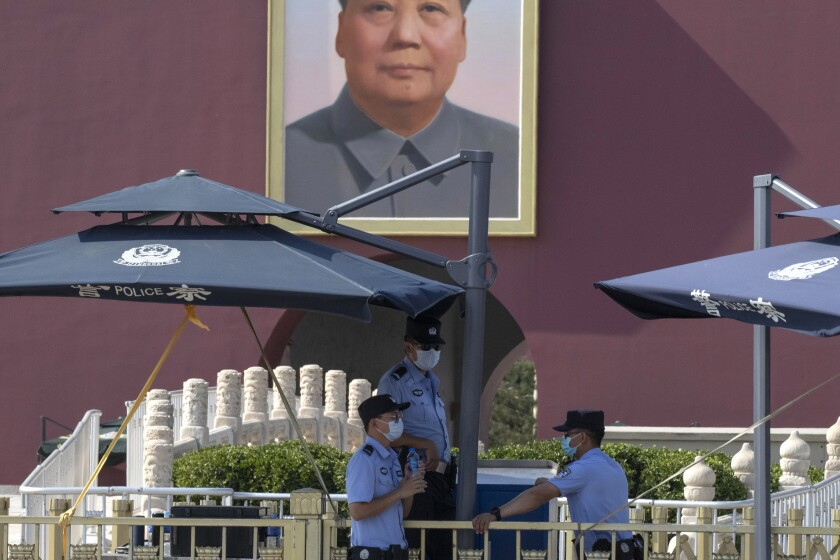 Chinese police officers wearing masks shelter in the shade near a portrait of Mao Zedong on Tiananmen Gate in Beijing Tuesday, June 16, 2020. Chinese authorities locked down a third neighborhood in Beijing on Tuesday as they rushed to prevent the spread of a new coronavirus outbreak that has infected more than 100 people in a country that appeared to have largely contained the virus. (AP Photo/Ng Han Guan)