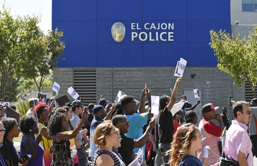 Protesters march past the headquarters of the El Cajon Police Department