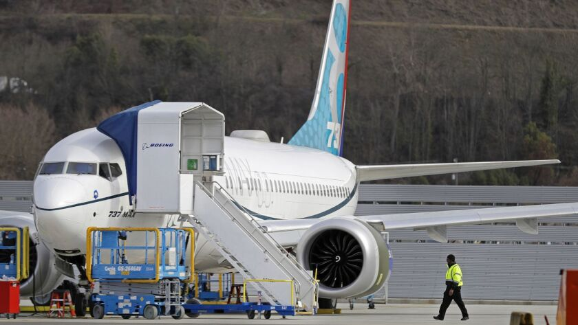 A worker walks next to a Boeing 737 MAX 8 airplane parked at Boeing Field, Thursday, March 14, 2019,