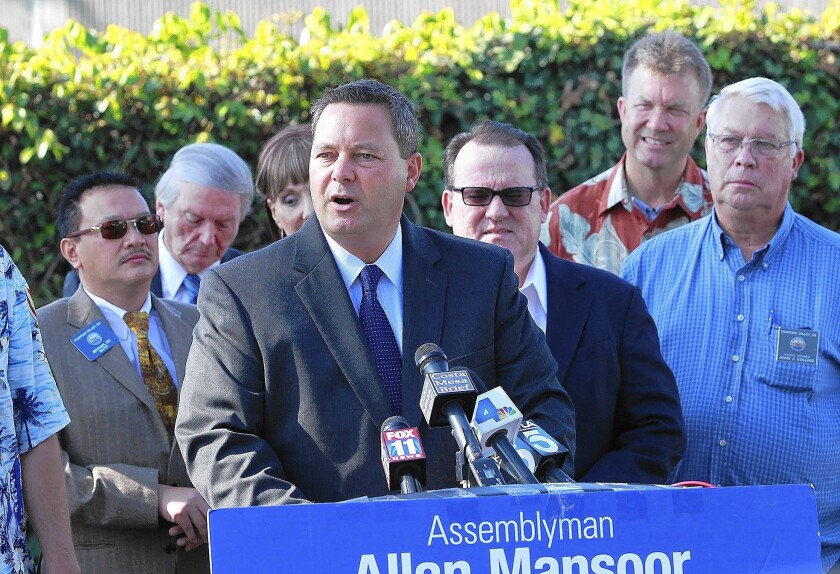 Assemblyman Allan Mansoor speaks at a press conference to declare opposition to the 405 Freeway toll lane proposal as officials from Orange County cities stand behind him in support Thursday.