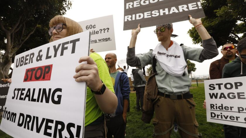 Lyft driver Jos Cashon, 28, left, joins fellow Uber and Lyft drivers during a one-day strike in protest for better wages and working conditions near Los Angeles International Airport in May.