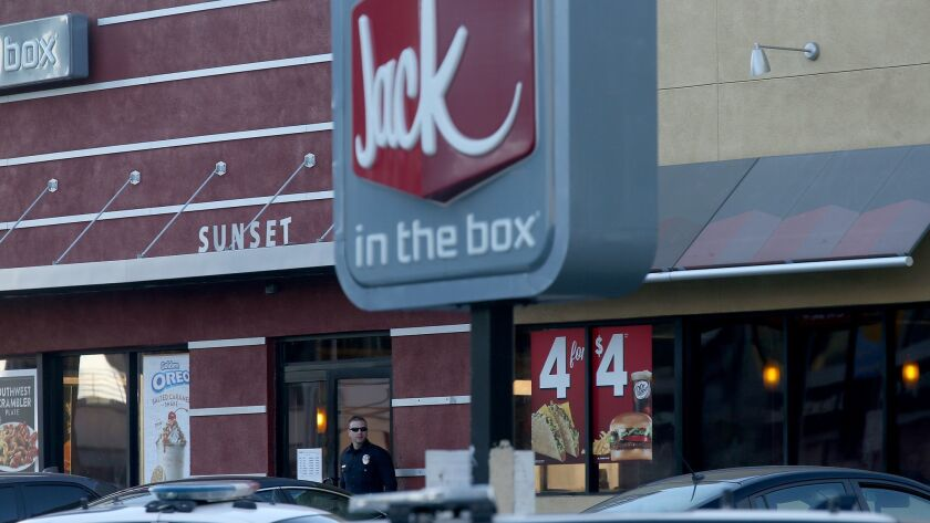 Two men were killed over two days in separate shootings at Jack in the Box restaurants. In this file photo, an LAPD officer stands guard outside a Hollywood restaurant where three people were stabbed and another was fatally shot in 2017.