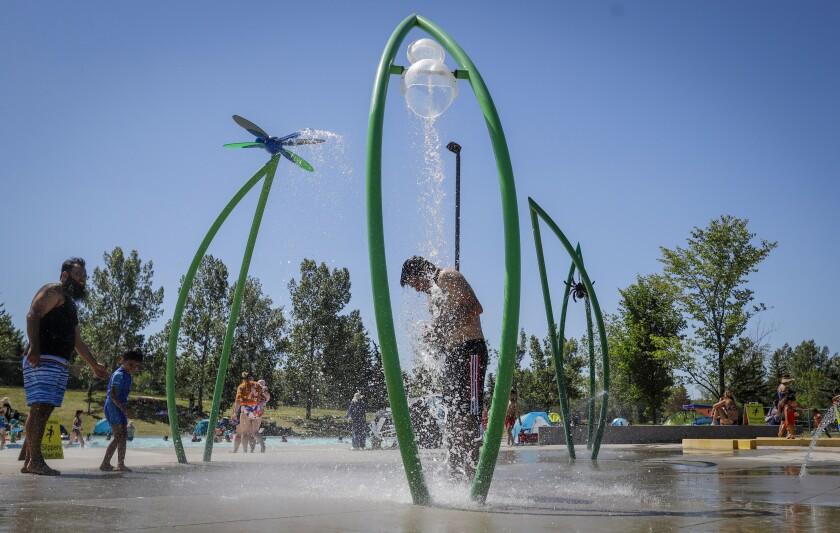 un hombre bajo una fuente para combatir el calor en un parque acuático de Calgary, Alberta.