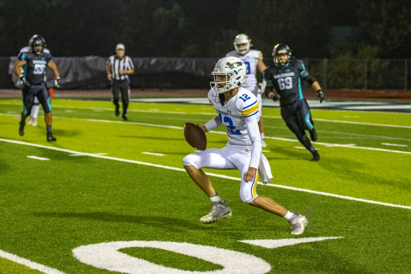 Fountain Valley quarterback Owen Tomko runs with the ball during Friday night's game.