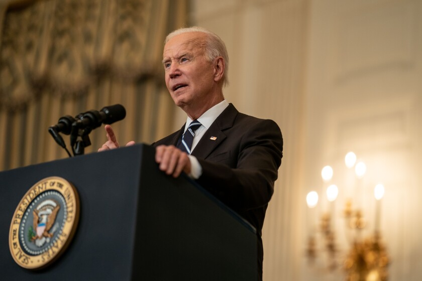 President Biden speaks from behind a lectern at the White House