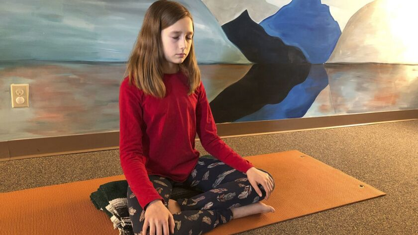 Aeva Schifferli, 12, demonstrates a stress-relieving breathing exercise at her mother's yoga studio in East Aurora, N.Y.