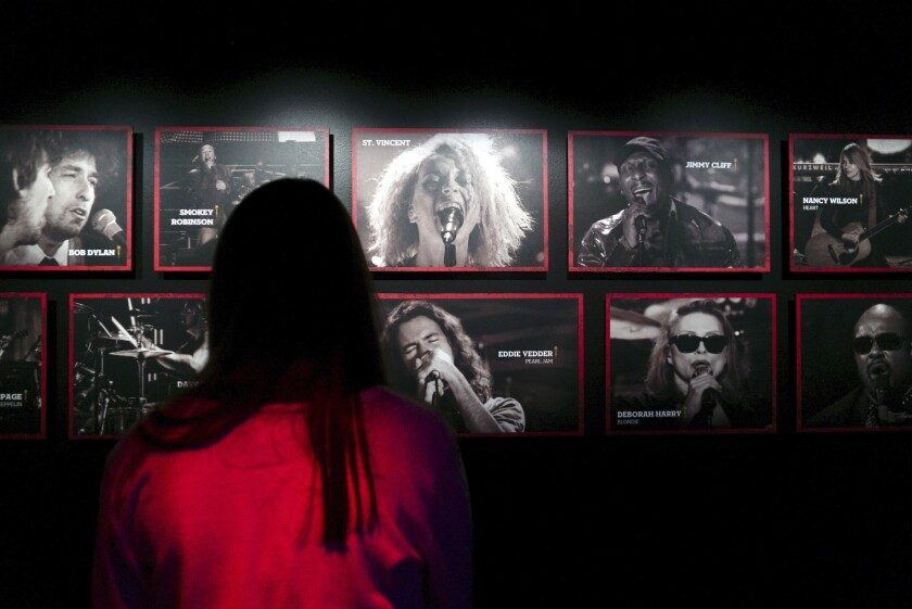 A woman looks at photos of Hall of Fame inductees at the Rock & Roll Hall of Fame in Cleveland.
