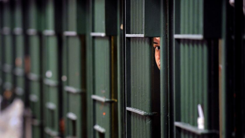 An inmate peaks through the bars at the Men's Central Jail in Los Angeles.