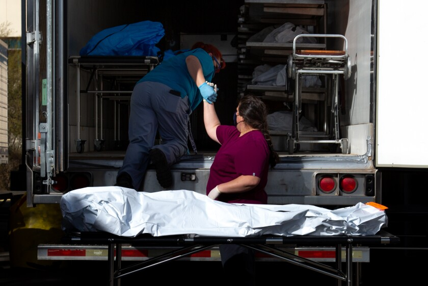 Employees prepare to move a body into a refrigerated semitruck at the Pima County medical examiner's office in Tucson.