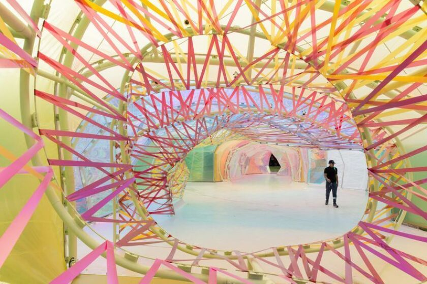 A view through pink ribbons to a structure sheathed in translucent polymer.