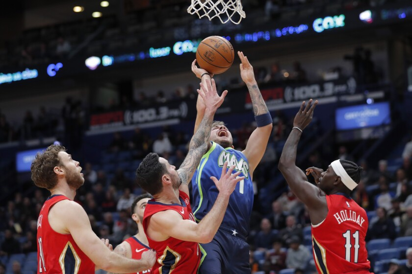 Dallas Mavericks forward Luka Doncic (77) shoots between New Orleans Pelicans forward Nicolo Melli, left, guard JJ Redick and guard Jrue Holiday (11) in the first half of an NBA basketball game in New Orleans, Tuesday, Dec. 3, 2019. (AP Photo/Gerald Herbert)