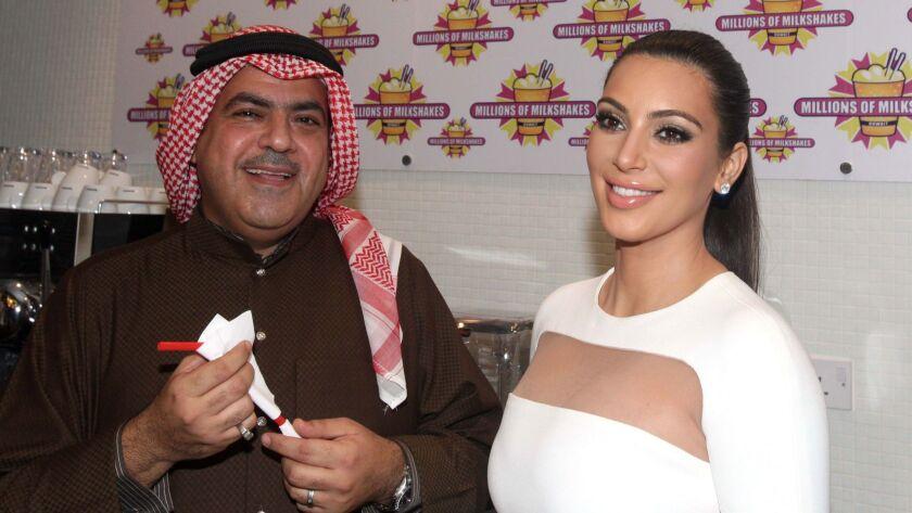 US celebrity Kim Kardashian (R) poses with Kuwaiti business man Ehab al-Aradi (L), during the openin