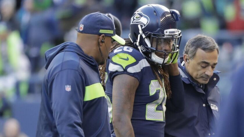 Seahawks cornerback Shaquill Griffin is helped off the field after sustaining an injury during the first half a game against the Arizona Cardinals on Dec. 30 in Seattle.