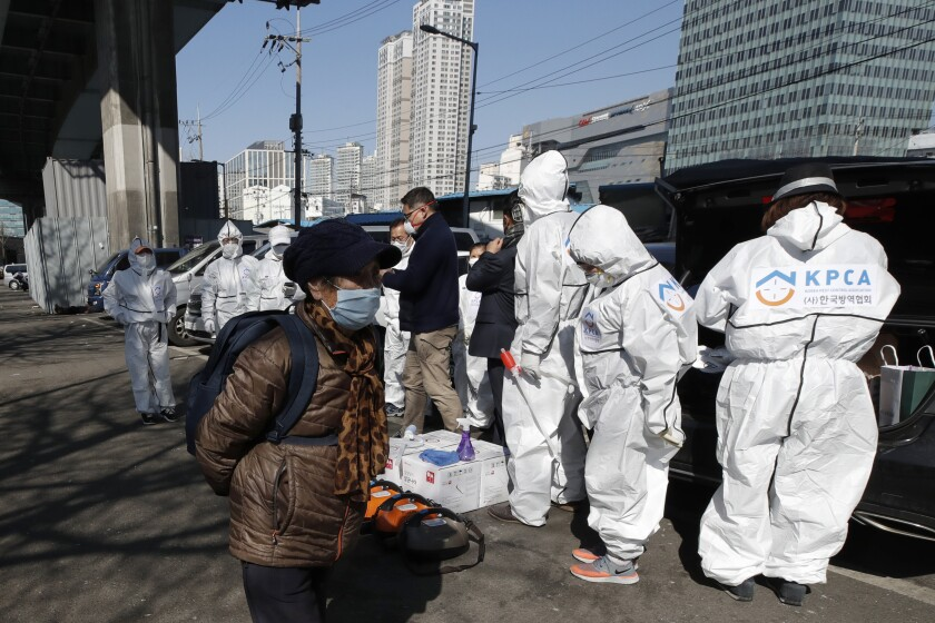 A woman wearing a face mask walks near workers wearing protective gears preparing to spray disinfectant as a precaution against the new coronavirus in Seoul, South Korea, Monday, March 16, 2020. For most people, the new coronavirus causes only mild or moderate symptoms, such as fever and cough. For some, especially older adults and people with existing health problems, it can cause more severe illness, including pneumonia. (AP Photo/Lee Jin-man)