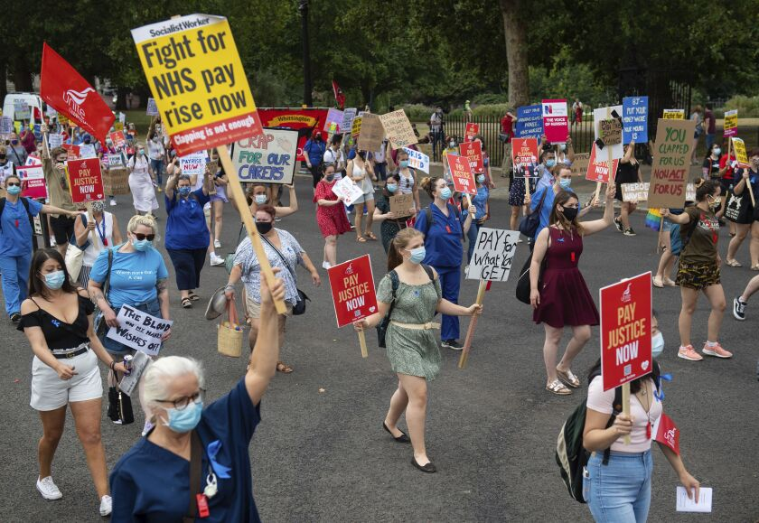 National Health Service (NHS) workers march from St. James' Park to Downing Street, London, Saturday Aug. 8, 2020, as part of a national protest over pay. Nationwide protests on Saturday are calling for government to address what they claim is many years of reduced wages, and are calling for a voice in plans for public sector pay increases. (Dominic Lipinski/PA via AP)