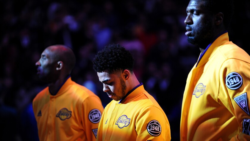 Lakers rookie D'Angelo Russell, center, listens to the national anthem between Kobe Bryant and Roy Hibbert before their game Wednesday night at the Staples Center.