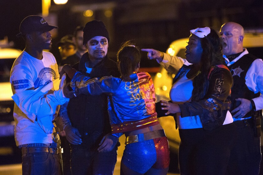A Chicago police officer tells several people dressed in costume to leave the scene of a shooting late Saturday.
