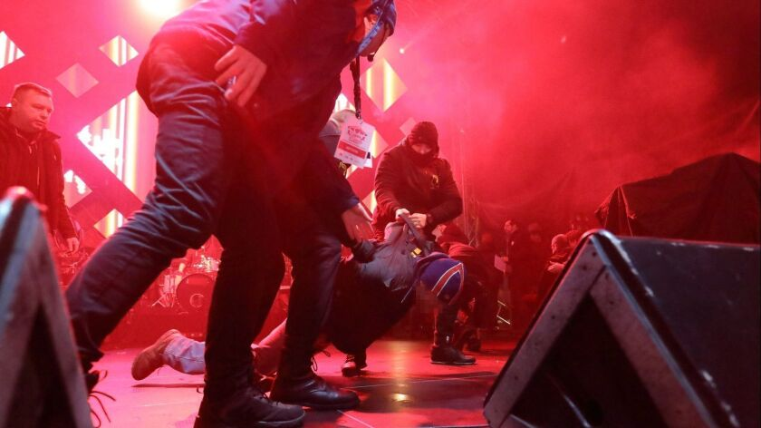 Security staff trying to stop a man after he attacked Mayor of Gdansk Pawel Adamowicz during the 27th finale of the Great Orchestra of Christmas Charity in Gdansk, Poland.