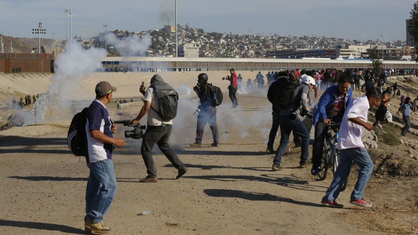 In this Nov. 25, 2018 file photo, migrants run from tear gas launched by U.S. agents, amid members of the press covering the Mexico-U.S. border, after a group of migrants got past Mexican police at the Chaparral crossing in Tijuana, Mexico.