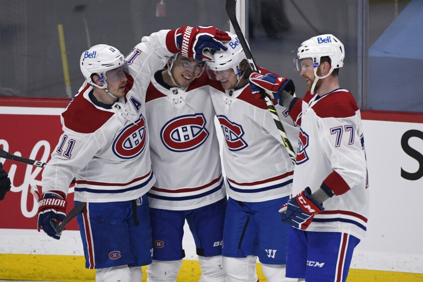 Montreal Canadiens' Brendan Gallagher (11), Nick Suzuki (14), Tyler Toffoli (73) and Brett Kulak (77) celebrate Toffoli's goal during second-period NHL hockey game action against the Winnipeg Jets in Winnipeg, Manitoba, Monday, March 15, 2021. (Fred Greenslade/The Canadian Press via AP)