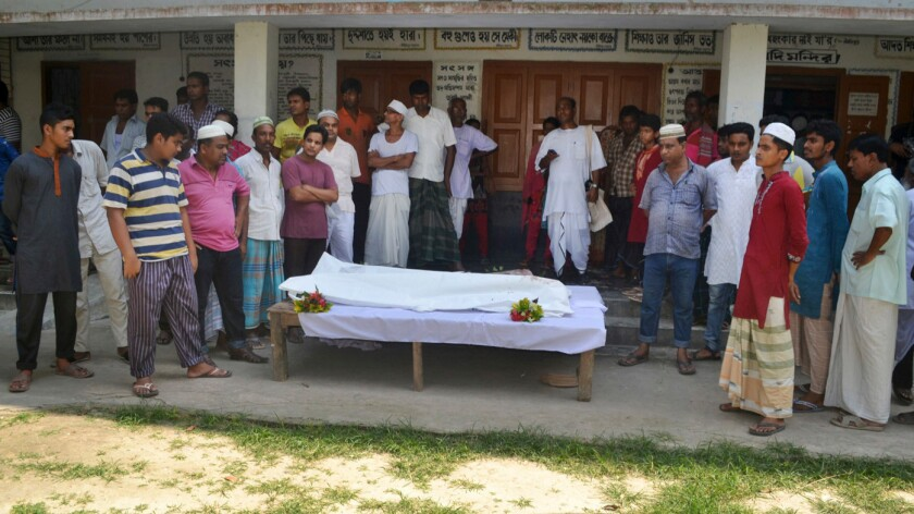 Locals surround the body on a Hindu man who was fatally attacked, the latest in a series of killings blamed on extremists.
