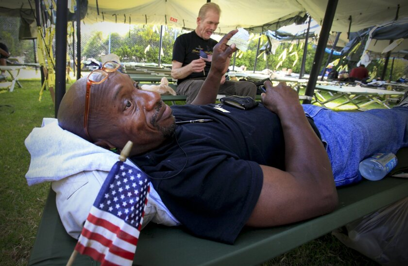 Navy veterans James Fields and Fred Bale relax on their sleeping cots during the annual Stand Down for Homeless Veterans at the athletic fields of San Diego High School.