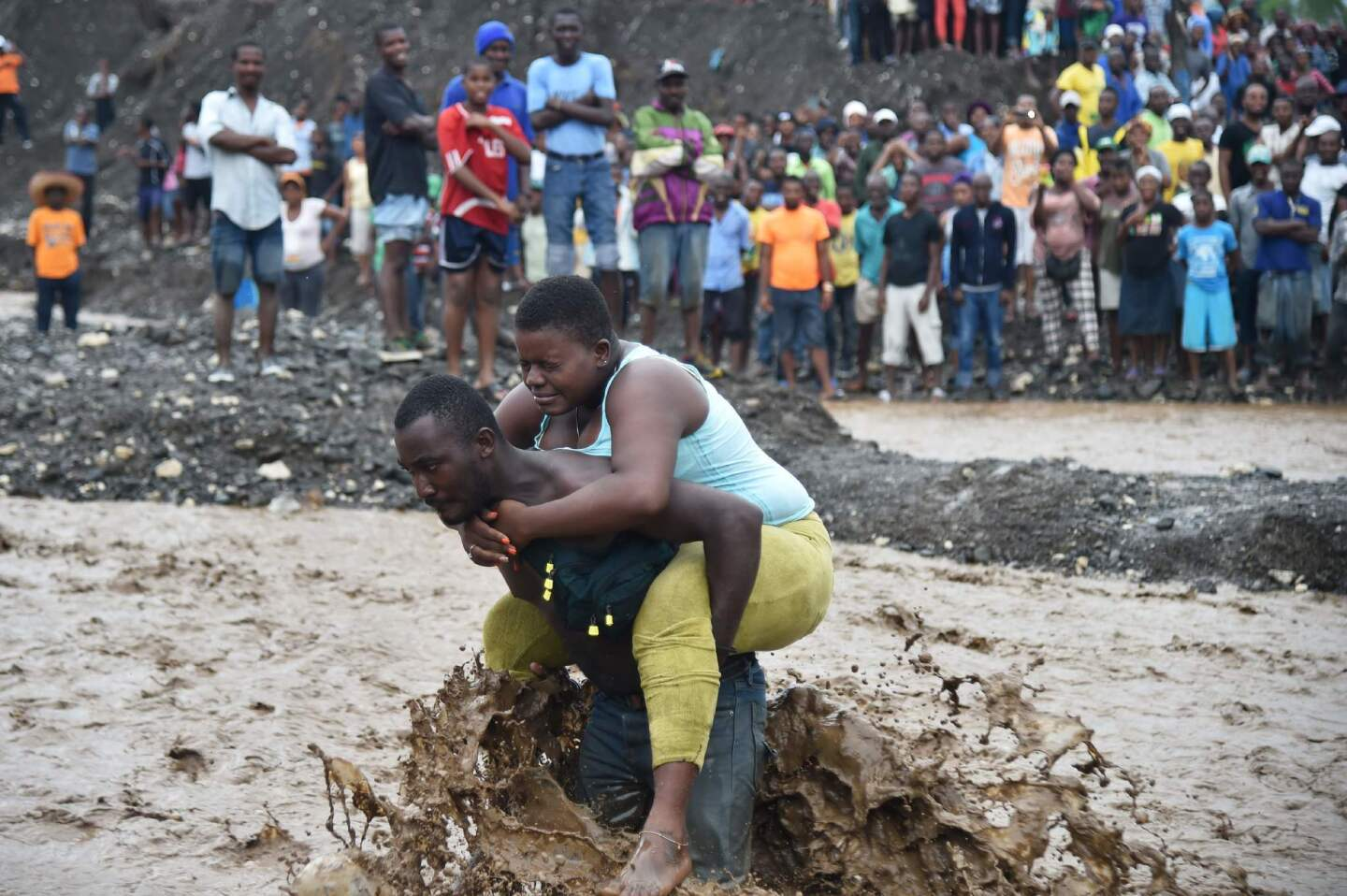A man carries a woman across a river at Petit Goave where a bridge collapsed during the rain from Hurricane Matthew, southwest of Port-au-Prince, Haiti.
