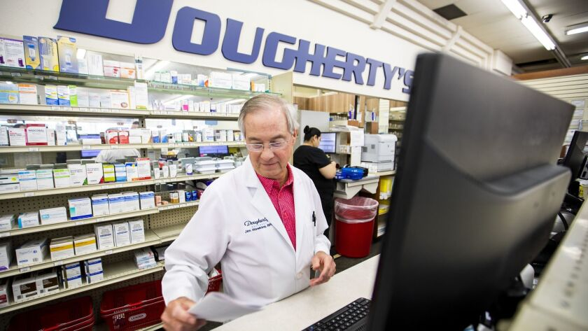 Pharmacist Jim Hawkins works behind the counter at Dougherty's Pharmacy in Dallas. Pharmacy managers and pharmacists had the second- and third-highest annual base pay, according to a Glassdoor report, at $146,412 and $127,120, respectively.