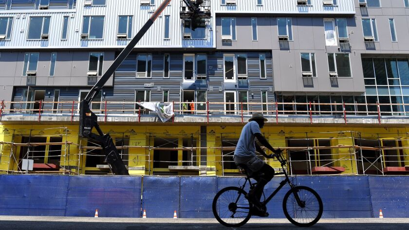 A bicyclist passes by construction in downtown Los Angeles on Aug. 3.