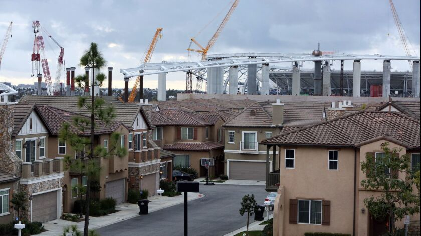 Construction of the Rams-Chargers Complex is seen behind the Renaissance Homes in Inglewood on Feb. 20.