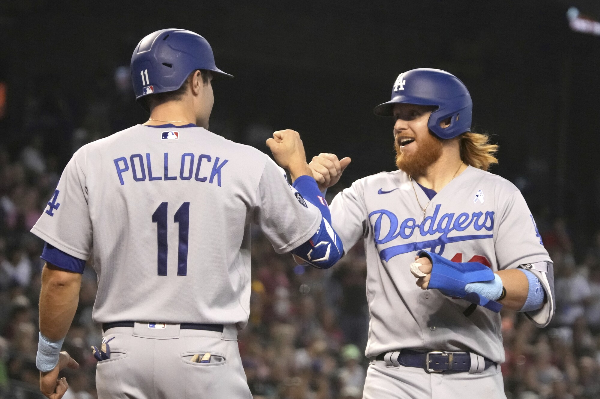 AJ Pollock and Justin Turner celebrate after scoring runs on a home run hit by Albert Pujols.