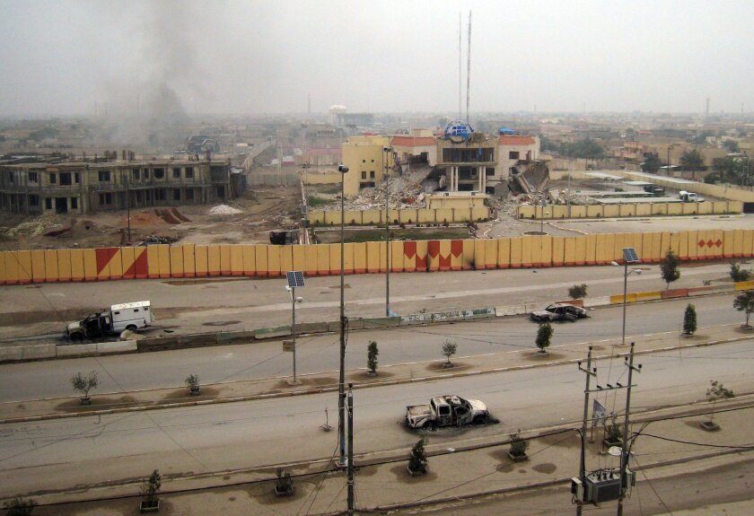An empty street shows burned vehicles as buildings including a provincial government building, center in the background, are seen damaged in Fallujah, 40 miles (65 kilometers) west of Baghdad, Iraq, Friday, Jan. 3, 2014. Provincial spokesman Dhari al-Rishawi said Iraqi security forces and allied tribesmen are pressing their campaign to rout al-Qaida from Fallujah and Ramadi, two main cities in the western Anbar province. (AP Photo)
