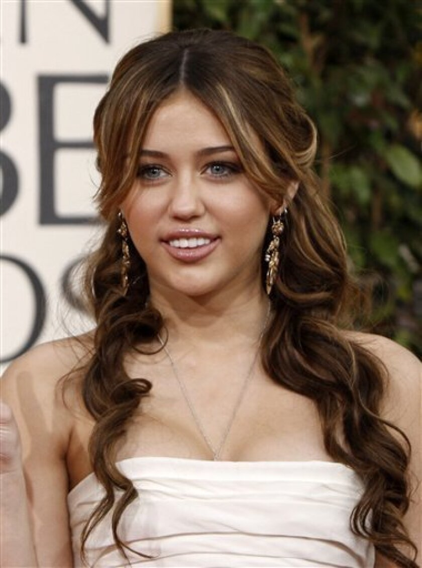 In this Jan. 11, 2009 file photo, Miley Cyrus arrives at the 66th Annual Golden Globe Awards in Beverly Hills, Calif. (AP Photo/Matt Sayles, file)