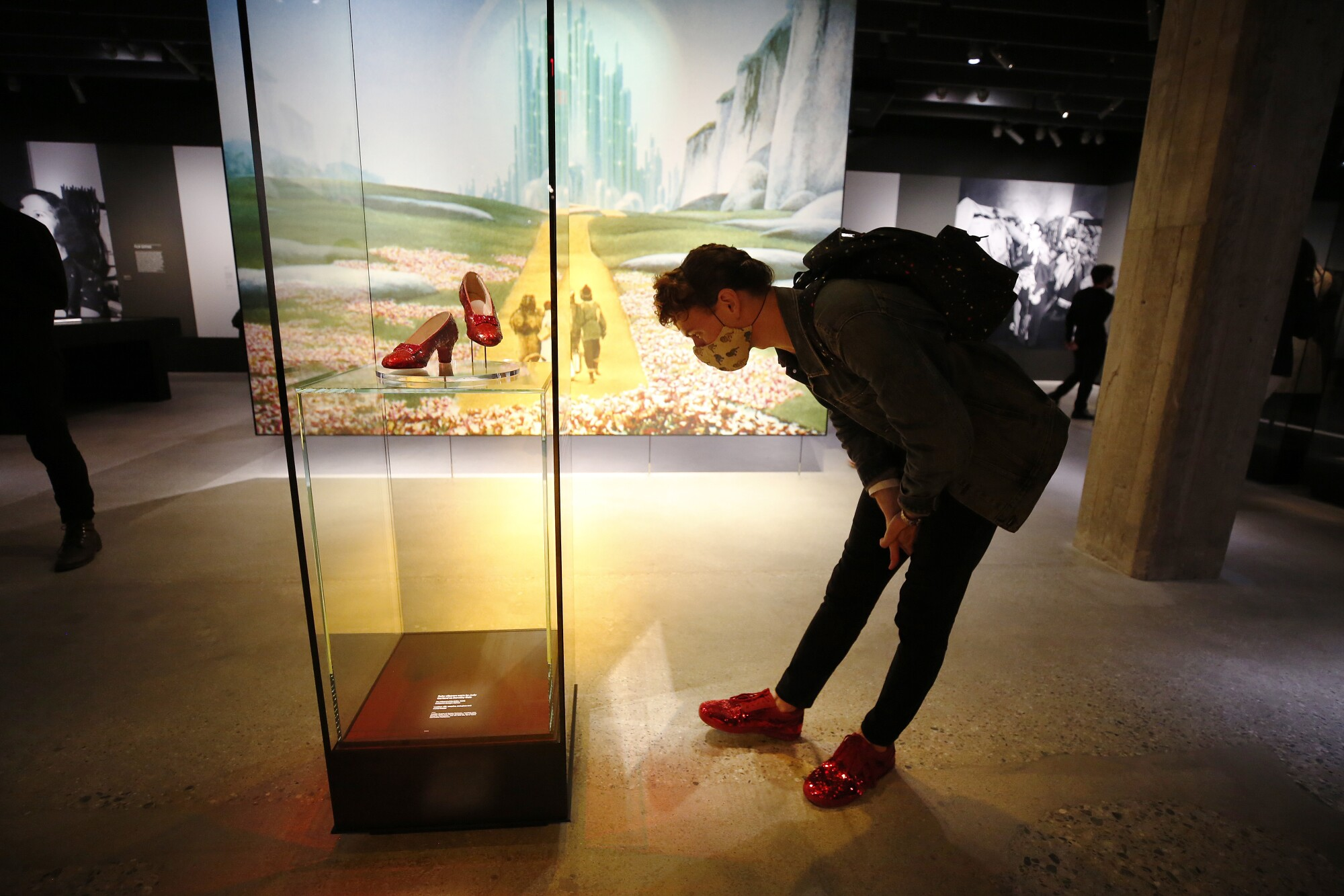 """A person bends to look at a display case containing Dorothy's ruby slippers from """"The Wizard of Oz."""""""