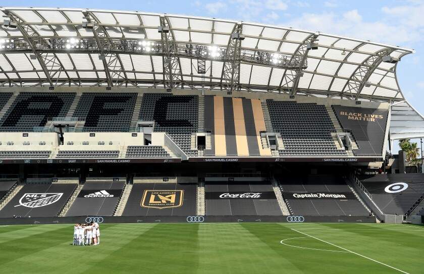 Galaxy soccer players gather at an empty stadium before a game against LAFC at Banc of California