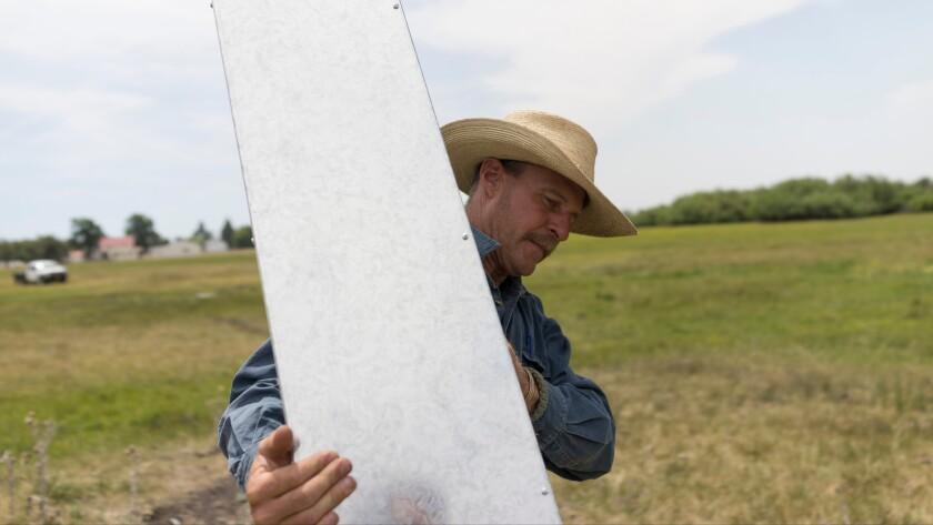 Sean Dunagan helps install the artists' border marker in New Pine Creek, Calif.