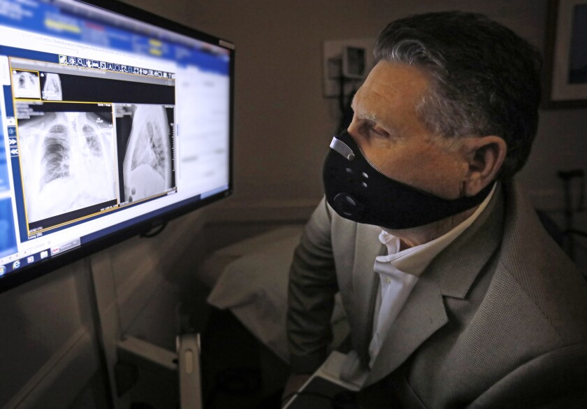 Lung transplant patient Fred Rorabaugh of Oceanside, wearing an air filtration mask because his immune system is suppressed, looks at a digital x-ray that shows his recently-transplanted right lung. The new lung is the darker shape on the left side of the photograph.