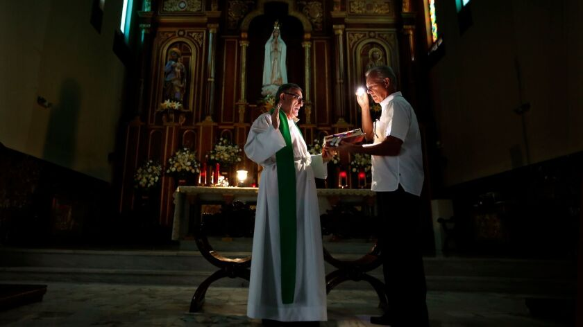The Rev. Elias Lorenzana says Sunday Mass inside Nuestra Señora de Fatima Catholic Church in the Hat