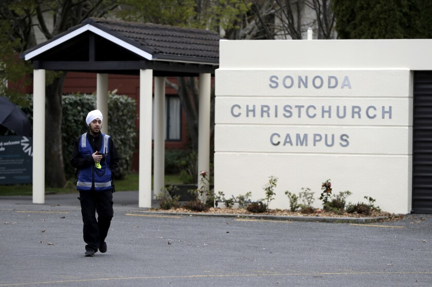 A security guard keeps watch outside student accommodation at Canterbury University in Christchurch, New Zealand, Wednesday, Sept. 25, 2019. New Zealand's education minister called for an investigation Wednesday after reports that a student's body lay undiscovered in a university dorm room for nearly eight weeks. (AP Photo/Mark Baker)