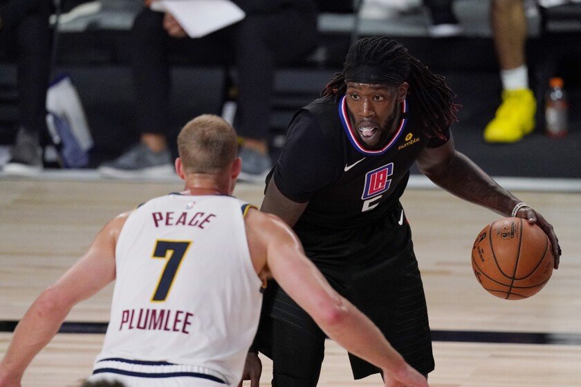 Clippers center Montrezl Harrell is defended by Nuggets center Mason Plumlee (7) during Game 1 on Sept 3, 2020.