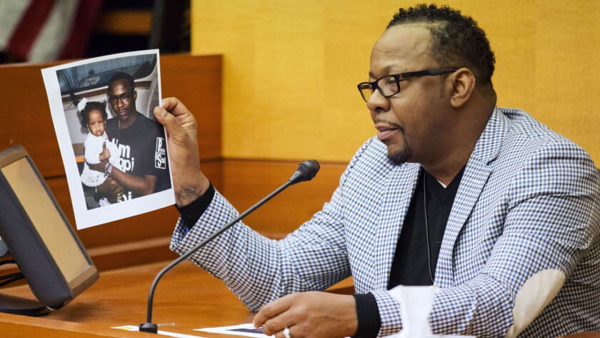 Bobby Brown holds up a picture of himself with Bobbi Kristina Brown while testifying in a wrongful death case against her partner, Nick Gordon, in Atlanta on Thursday.