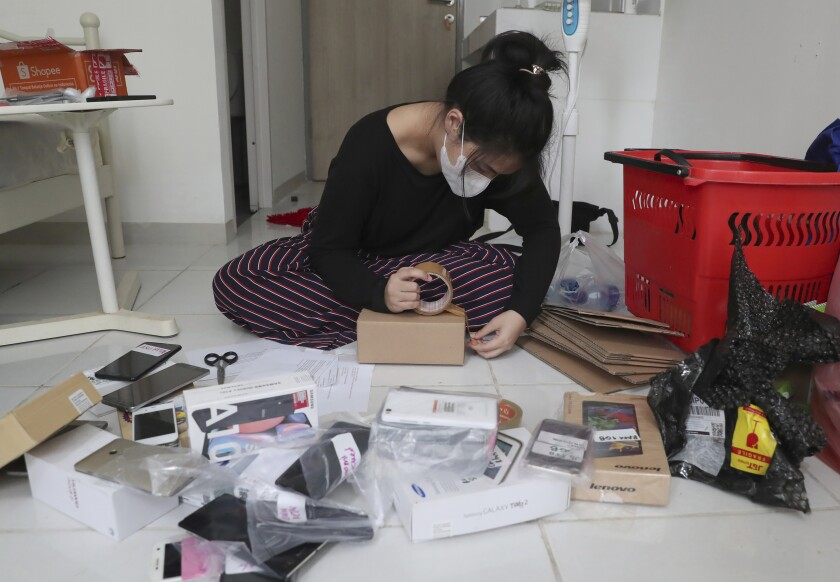 Indonesian journalist Ghina Ghaliya pack used mobile phones before shipping them to underprivileged children who lack internet access to study online, at her apartment in Tangerang, Indonesia, on Sept. 25, 2020. When a garbage collector came to Ghaliya's house and asked if she had an old mobile phone his children could use to access the internet, it sparked an idea for a broader campaign to help students stuck at home by the coronavirus. (AP Photo/Tatan Syuflana)