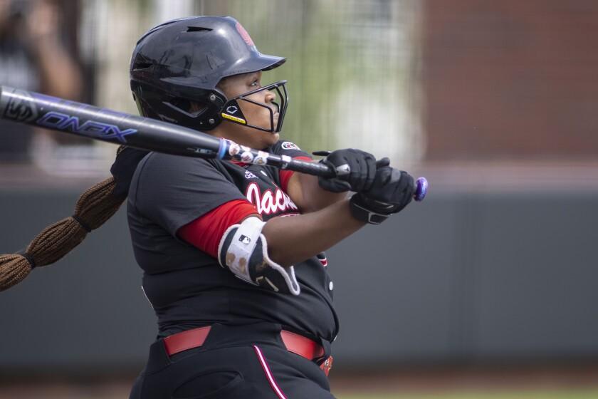 A softball batter follows through on her swing.