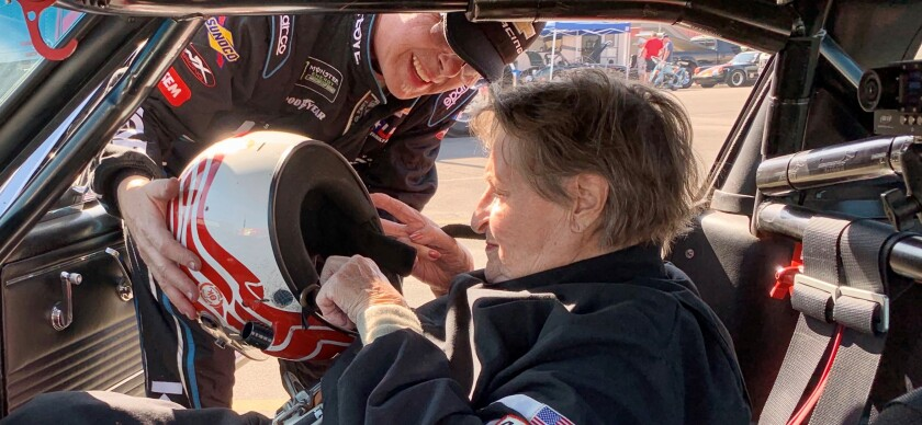 Nancy Pinta, 84, of Escondido puts on her safety helmet with help from driver Lance Smith of San Diego, who offered to take the onetime powder puff stock car racer for a spin in his 1966 Mustang at the Auto Club Speedway in Fontana on Saturday, Feb. 8.